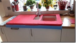 1.3 Mat showing additional strip of padding between the top and the blue edging using offcuts, to cater for raised lip of ceramic sink, and to ensure water drains back into the sink and not onto the user.