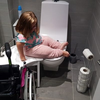 Girl sliding from the transfer stool over to the toilet